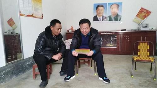 图为:冯世龙看望贫困户