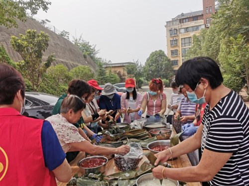 图为:市残联党员干部与居民代表共同包粽子