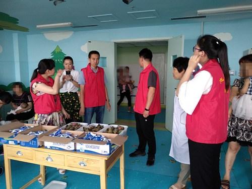 图为县残联志愿者为残疾儿童带去了粽子和酸奶等端午节慰问品