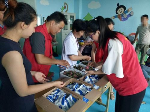 图为县残联志愿者和康复医师为残疾儿童分发粽子和酸奶