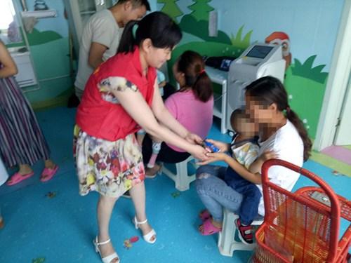 图为县残联志愿者亲自把热气腾腾的粽子和酸奶递到残疾儿童手中