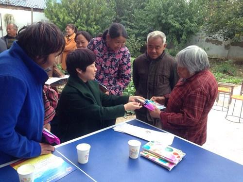 图为想残联办证中心主任李凤敏为贫困人员发放宣讲资料