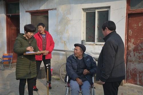 图为残联办证人员深入残疾人家中送服务