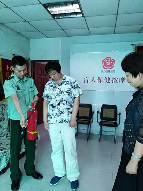 图为向盲人保健按摩机构经营者教授灭火器使用知识
