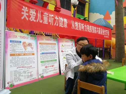 图为社区医生为儿童检查耳朵
