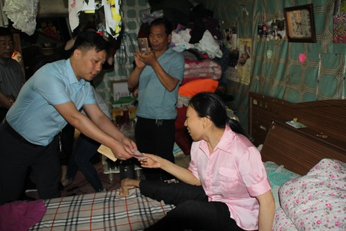 图为李继龙秘书长向残疾人发放慰问金