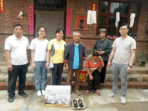 图为基金会理事财务部主任张玉萍(左三)向残疾人发放慰问金和爱心物资