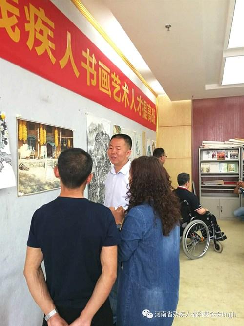 图为省美协主席刘杰对残疾人书画家何春亮作品进行指导