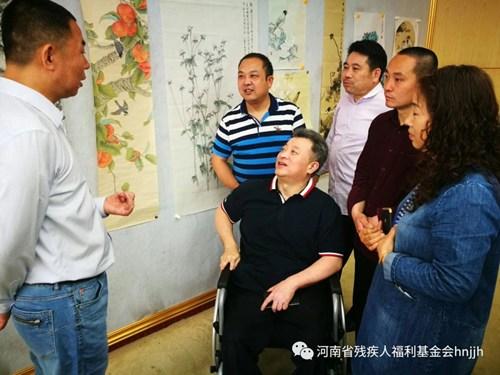图为省残联理事刘峥伟同省美协主席及学员进行交流