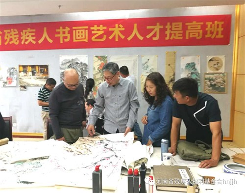 图为省美协副主席封曙光对残疾人艺术家进行作品指导