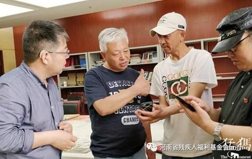 图为残疾人画家李景明、贺志强、刘德山向省美协副主席丁昆请教